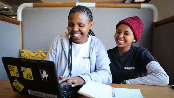 Two young women at the front of the computer, they are both part of our program to create jobs for youth in South Africa