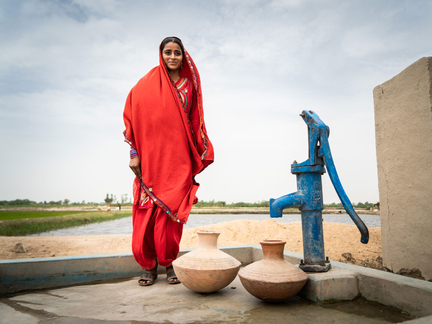 Sughra, 20, with a WaterAid installed water pump in the villlage of Muhammad Urs Sehejo in the Thatta District, Sindh Province, Pakistan.