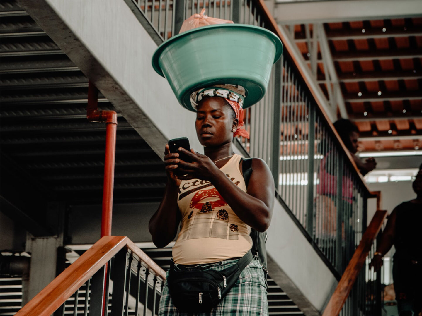 Woman in Africa reading her phone while carrying a basket on her head.